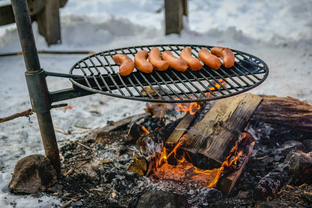 Campfire with sausages cooking on top