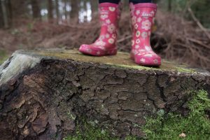 Girl walking in a forest with wellington boots