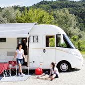 family standing outside motorhome with open awning